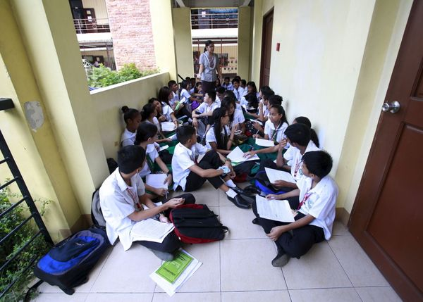 Manila, Philippines --- Teacher Kristine Passag holds a Values Education class for ninth-grade students in a hallway of Timot