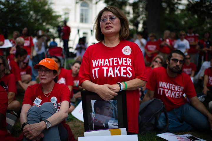 WASHINGTON, DC - SEPTEMBER 10: Maria Pike, 61, of Chicago, cries as she listens to a speaker during the event. She holds a ph