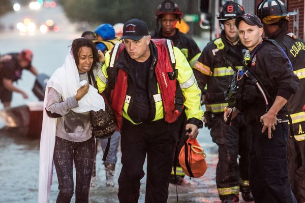 Charlene Stennis is escorted to safety after her son was rescued from a stranded vehicle ona flooded roadway in Columbi