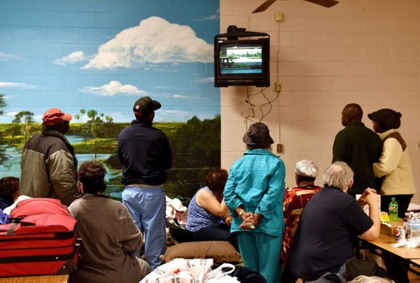Flood-displaced residents listen to the news at a temporary shelter at St. Andrews Middle School in Columbia, South Carolina.