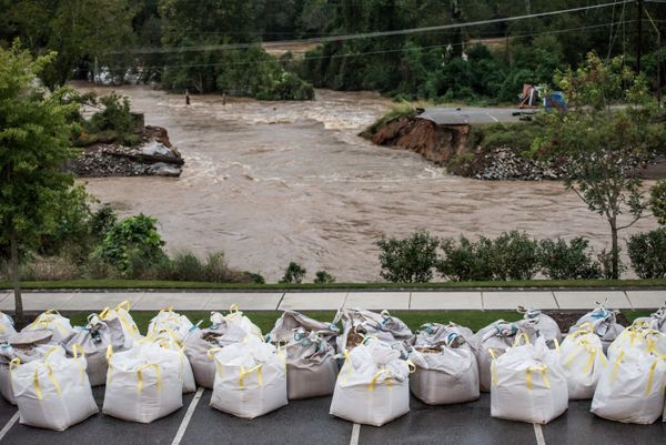 Floodwaters rush through the breach of the Columbia Canal as emergency workers prepare giant sandbags to plug the hole.