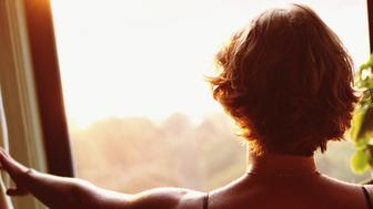 WOMAN LOOKING OUT WINDOW AT SUNRISE