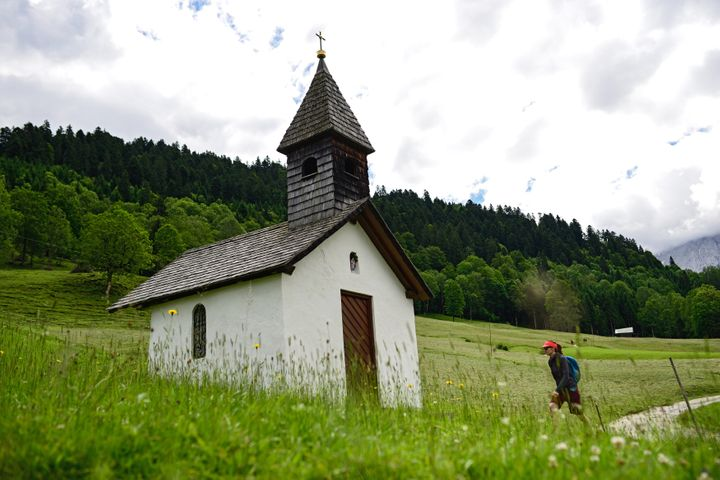 A hiker walks towards a small chapel in the Bavarian Alps on June 24, 2015, near Garmisch-Partenkirchen, Germany.