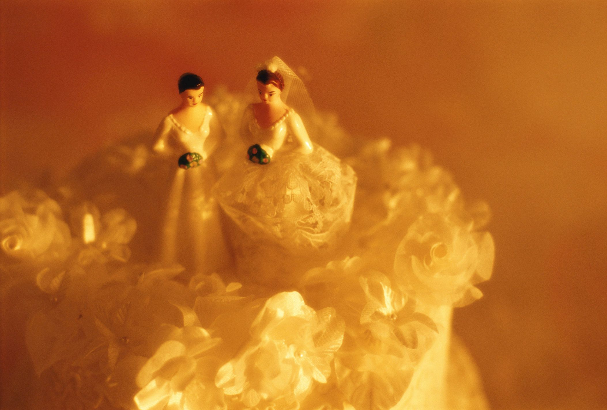 Two bride figurines atop wedding cake, elevated view