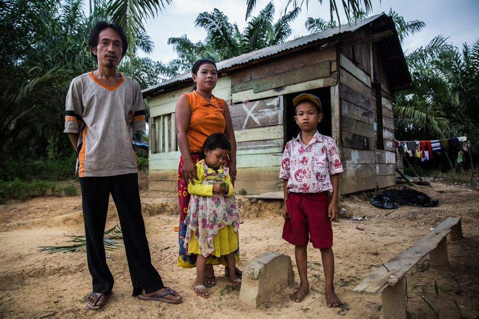 Revan Pragustiawan with his parents and one of his two sisters in front of the house his family built after a palm oil compan
