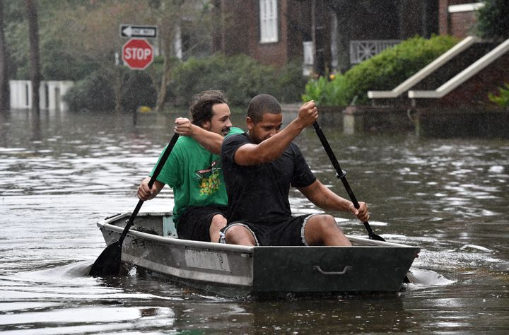 Two men row a boat on a flooded street in downtown Charleston, South Carolina on October 4, 2015.