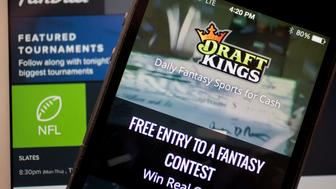 The DraftKings Inc. app and FanDuel Inc. website are arranged for a photograph in Washington, D.C., U.S., on Monday, Oct. 5, 2015. Fantasy sports companies DraftKings Inc. and FanDuel Inc. raised a total of $575 million in July from investors including KKR & Co., 21st Century Fox Inc. and Major League Baseball to attract players to games that pay out millions of dollars in cash prizes in daily contests. Photographer: Andrew Harrer/Bloomberg via Getty Images