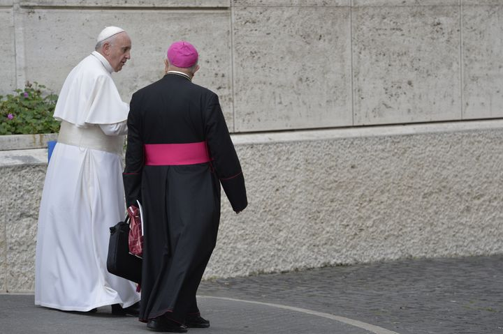 Pope Francis (L) leaves after the second morning session of the Synod of bishops on the Family at the Vatican on October 6, 2