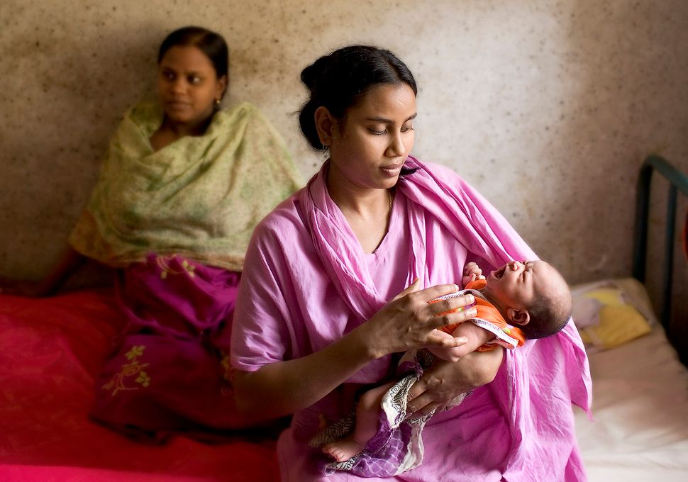 In a clinic outside of Dacca, Bangladesh, a nurse attends a teenage mother's baby. The young mother, who is 15 years old, is