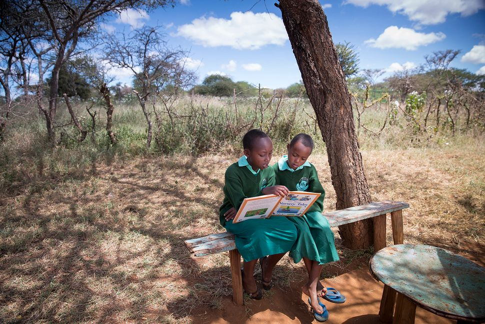 Two young Maasai girls doing homework outside one of the mud huts in their villages.
