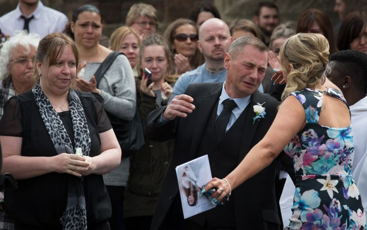 APRIL 17: Darren Galsworthy (C) is comforted after he released a dove following the memorial service at St Ambrose Church for