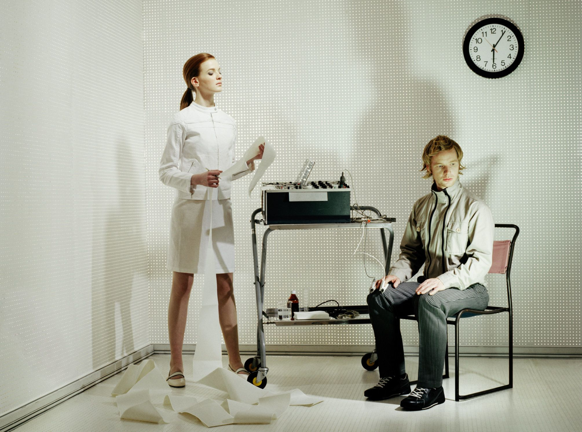 Young woman conducting lie detector test on man