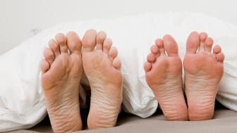 feet of mature couple peering under bedcover