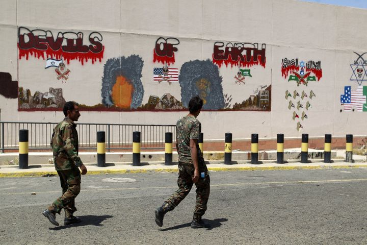 Yemeni security guards walk past an anti-Saudi and U.S. graffiti sprayed on the wall of the compound of the U.S. embassy in t