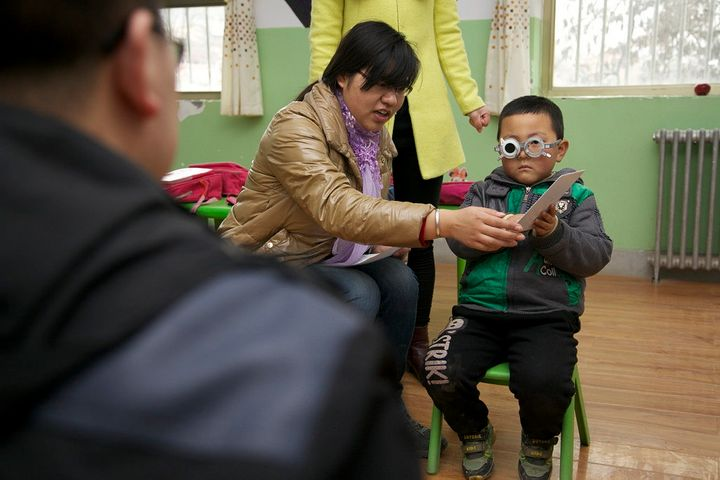 A child takes an eye exam administered by REAP and CEEE.