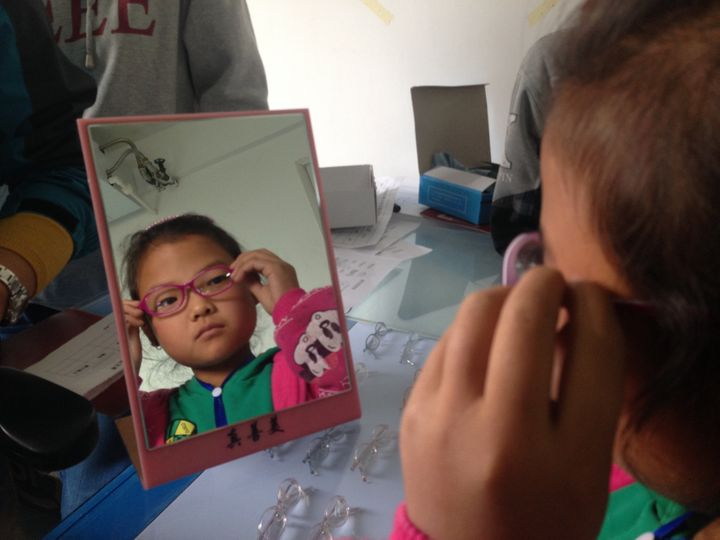 A girl tries on her first pair of glasses at the Qin'an County Hospital.