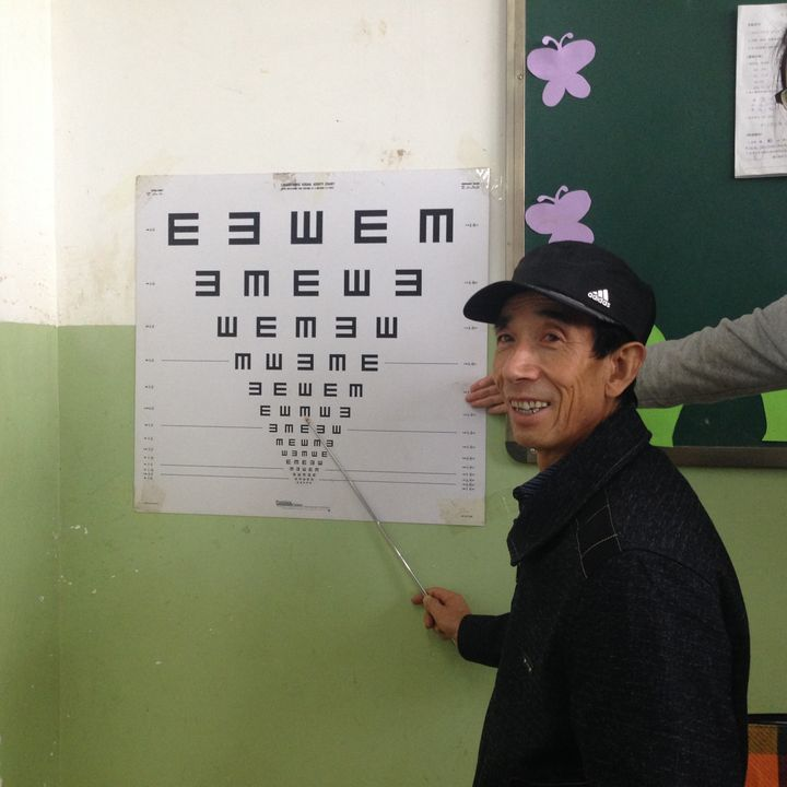 An elementary school teacher practices administering an eye exam during training.