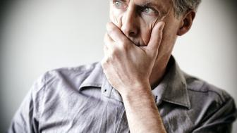 Man in his forties holding his face in his hand, appearing to be very worried or stressed.