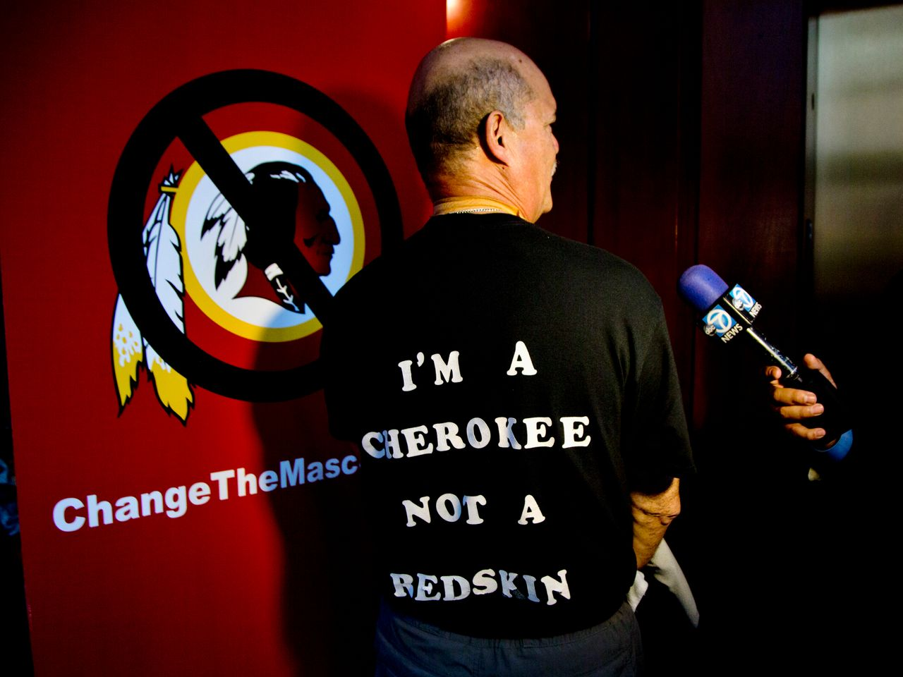 Verlin Deer In Water, a member of the Cherokee Nation of Oklahoma shows his t-shirt during an interview in Washington, Monday, Oct. 7, 2013, calling for the Washington Redskins NFL football team to change its name.