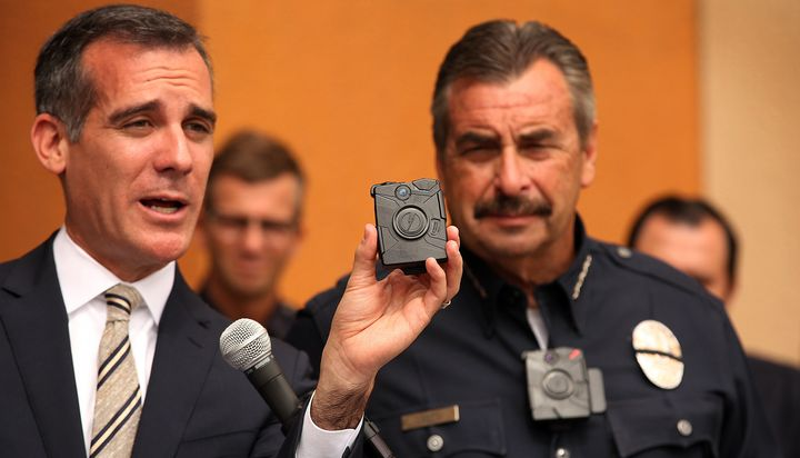 Los Angeles Mayor Eric Garcetti, left, with LAPD Chief Charlie Beck, right, who is wearing a body camera, shows off the new L
