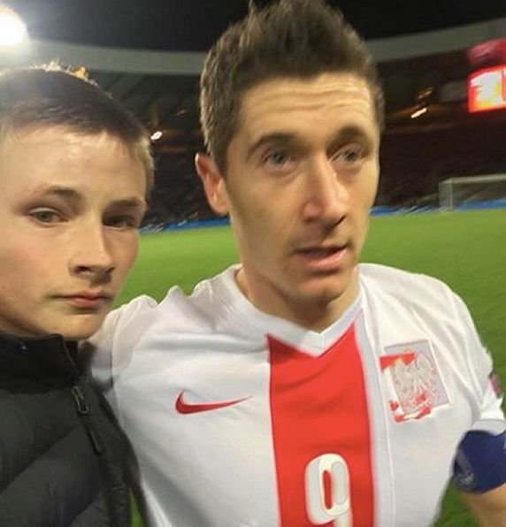 A young Scottish soccer fan poses with a bewildered Robert Lewandowski