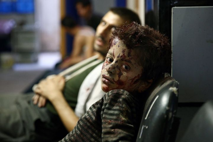 A Syrian boy waits to receive treatment at a makeshift hospital following reported airstrikes by government forces in the reb