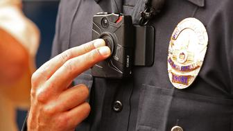 LOS ANGELES, CA -  SEPTEMBER 04:  Los Angeles Police Officer Jim Stover, with Information Technology Bureau demonstrates how an officer turns on the new LAPD body camera during a press conference at LAPD Mission Division Friday September 4, 2015 as they talked about the rollout of the agency's officer body cameras. The rollout of the body cameras began last Monday at LAPD's Mission Division in the north San Fernando Valley when officers received final instructions on using the cameras during roll call training sessions. About 1,000 video were recorded during the first two days of operation, according to Mayor Eric Garcetti. (Photo by Al Seib/Los Angeles Times via Getty Images)