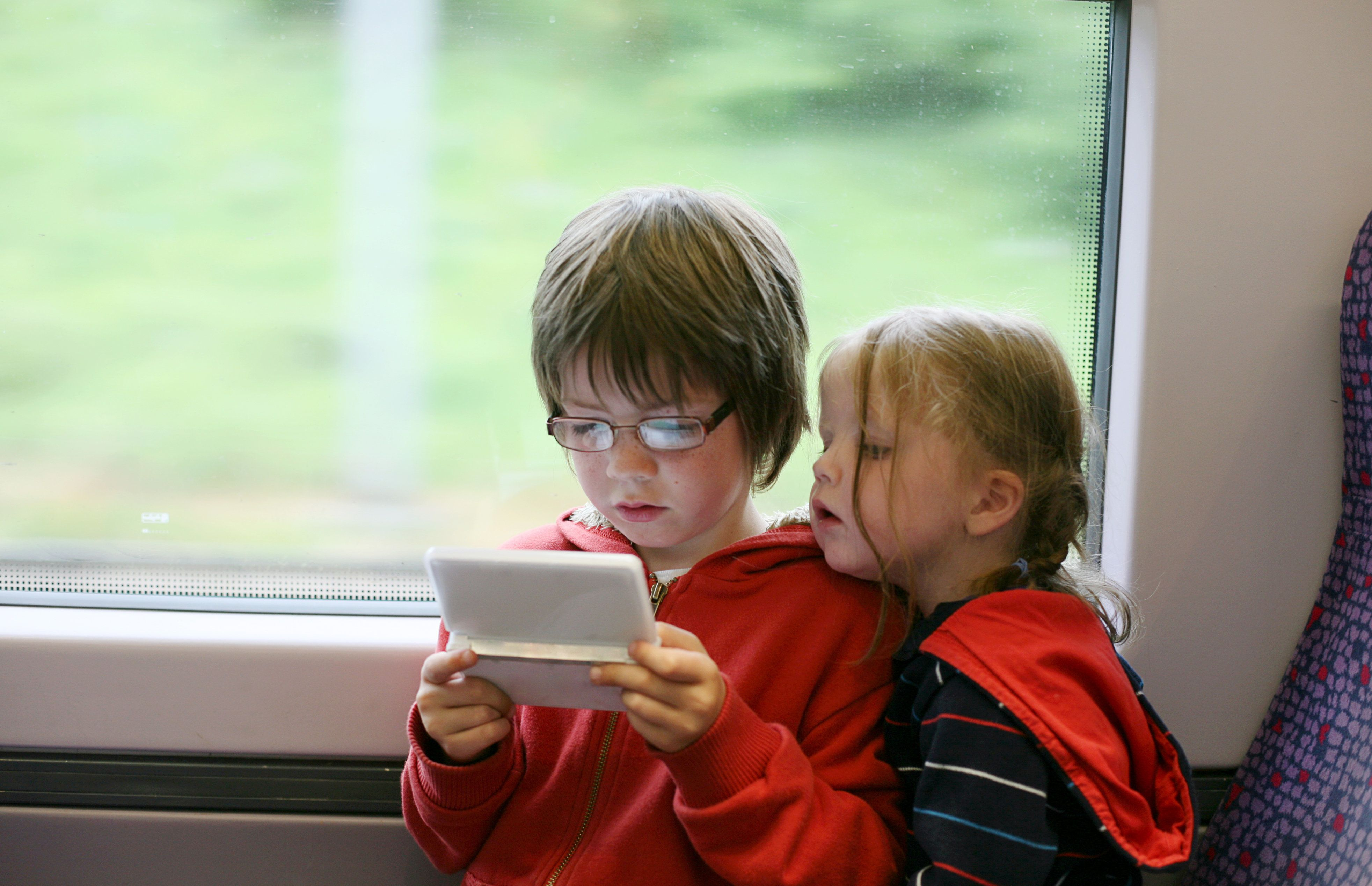 Boy and girl in train journey concentrating on handheld video game console.