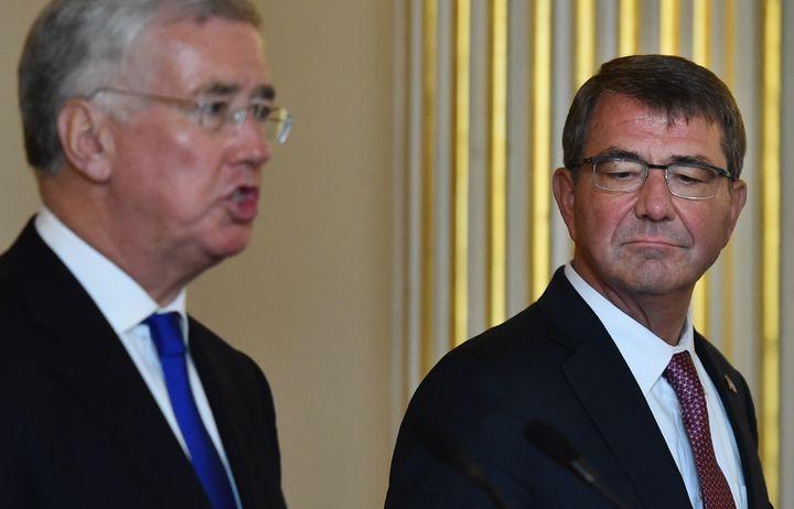 British Defence Secretary Michael Fallon (L) speaks as US Secretary of Defense Ashton Carter (R) listens at a joint press con