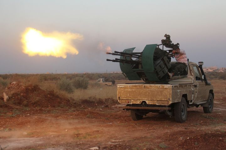 Rebel fighters fire a heavy machine gun during clashes with Syrian pro-government forces on the frontline facing Deir al-Zogh