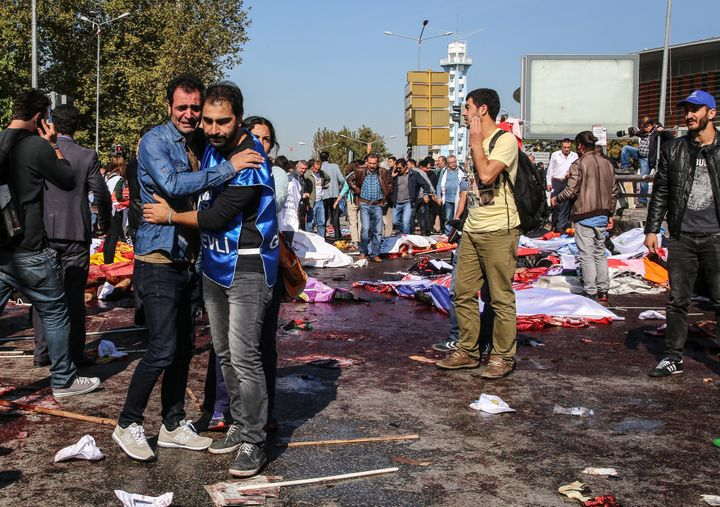 Survivors stand amongst the dead at the blast scene.