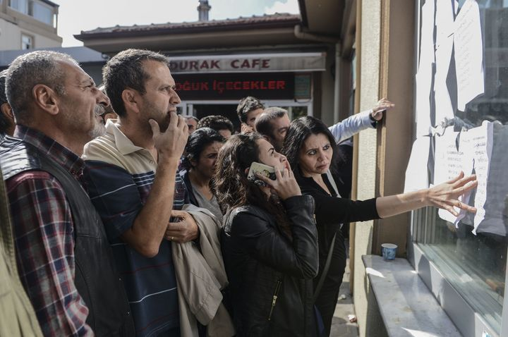 People check a list of the people who were injured in the blasts at the Ankara Numune hospital.