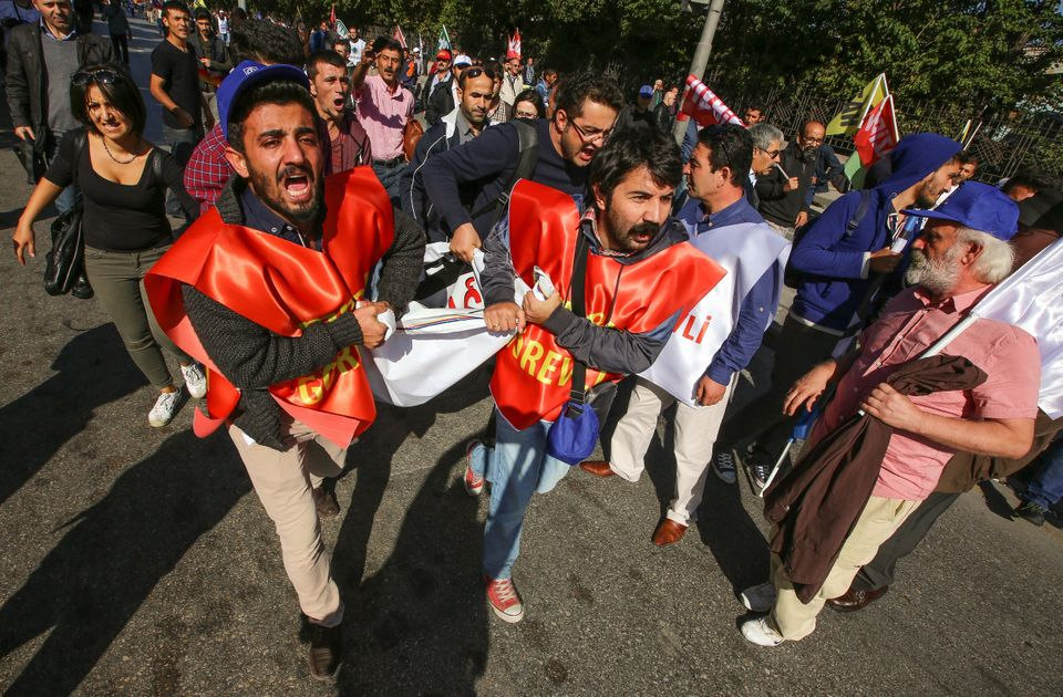 People carry a wounded man at the blast site in Ankara, Oct. 10, 2015.