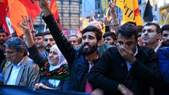 Demonstrators chant slogans and flash the V-sign during a rally to protest against the bombing in Ankara earlier, in central Istanbul, Saturday, Oct. 10, 2015. Thousands of protestors flooded the main street in central Istanbul shouting slogans condemning the twin bombings that killed dozens of people in nations capital. The two bomb explosions targeted a peace rally, that was aimed to call for an end to the renewed violence between Kurdish rebels and Turkish security forces. (AP Photo/Lefteris Pitarakis)