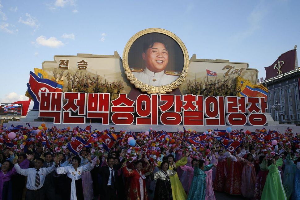 Parade participants wave flowers in front of a portrait of Kim Jong Un.