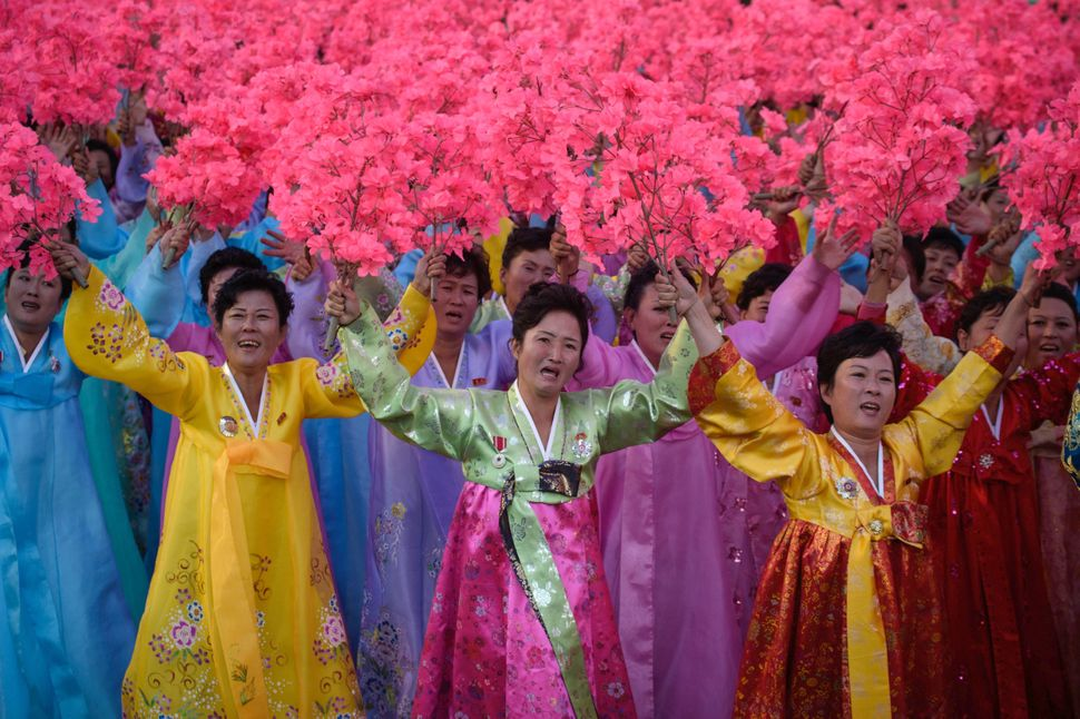 "North Koreans wearing traditional ""hanbok"" dresses wave flowers during a military parade Saturday, Oct. 10, 2015."