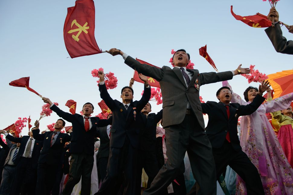 Participants wave flowers towards North Korean leader Kim Jong Un.