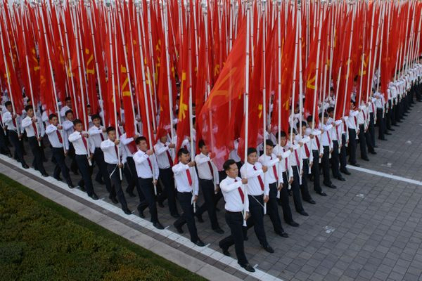 Participants hold flags as they pass through Kim Il Sung Square.