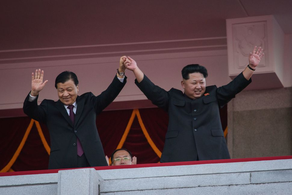 Kim Jong Un and Liu Yunshan wave to parade participants from a balcony.