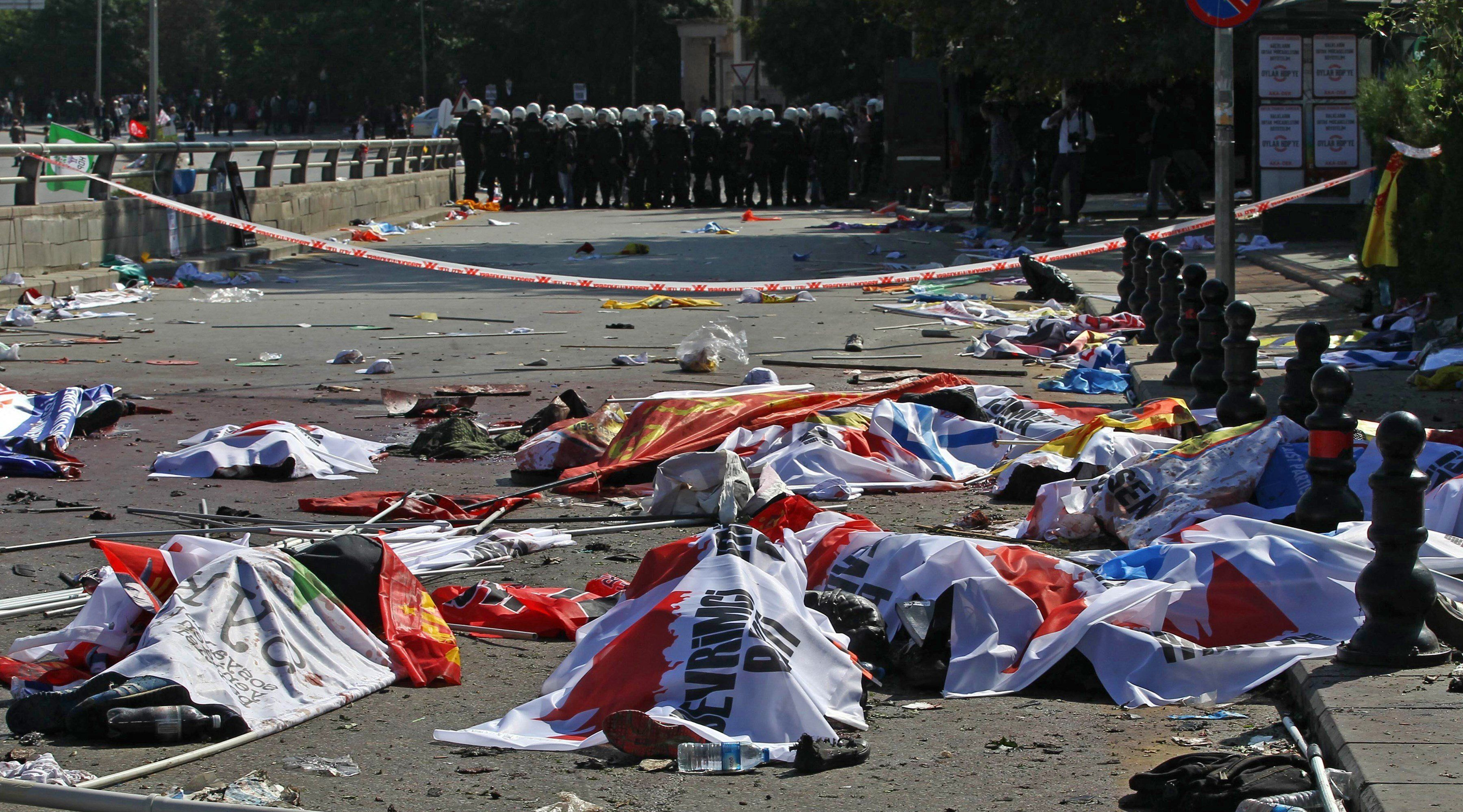 Turkish riot police forces (Rear) secure the site of twin explosions as victims' bodies on the street are covered with banners and flags, near the main train station in Turkey's capital Ankara, on October 10, 2015. At least 86 people were killed on October 10 in the Turkish capital Ankara when bombs set off by two suspected suicide attackers ripped through leftist and pro-Kurdish activists gathering for an anti-government peace rally, the deadliest attack in the history of modern Turkey. AFP PHOTO / ADEM ALTAN        (Photo credit should read ADEM ALTAN/AFP/Getty Images)