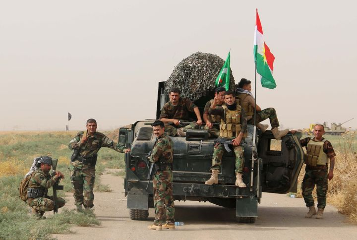 Iraqi Kurdish Peshmerga fighters pose for a photo next to a military vehicle bearing the Kurdish flag after they reportedly c