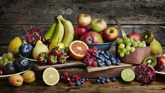 Assorted fruit including raspberries, blueberries, limes, lemons, mango, grapefruit, kiwi fruit, grapes, peaches and plums on plates and wooden boards against a wooden backdrop.