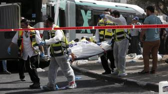 Israeli Zaka volunteers carry a body following a shooting attack on a bus in an east Jerusalem Jewish settlement adjacent to the Palestinian neighbourhood of Jabal Mukaber on October 13, 2015. Two attackers opened fire on a bus while another assailant carried out a car and knife assault in Jerusalem, leaving two people dead and five wounded in two separate incidents, Israeli authorities said. AFP PHOTO / THOMAS COEX        (Photo credit should read THOMAS COEX/AFP/Getty Images)