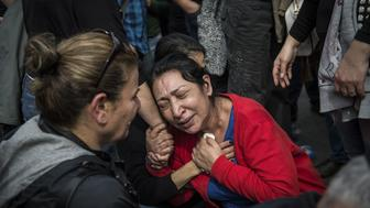 ANKARA, TURKEY - OCTOBER 11: People react as they gather to commemorate  at scene of yesterday's attack outside main train station in Ankara, Turkey on October 11, 2015. An explosion hit Ankara train station Saturday morning leaving 95 people dead and 160 others injured, as many people gathered outside the station for a peace demonstration to be held in nearby at Sihhiye Square. (Photo by Ozge Elif Kizil/Anadolu Agency/Getty Images)