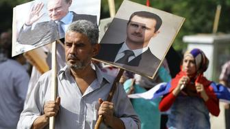 A Syrian man holding up portraits of President Bashar al-Assad and his Russian counterpart Valdimir Putin (L) joins several hundred people who gathered near the Russian embassy in Damascus on October 13, 2015 to express their support for Moscow's air war in Syria, just before two rockets struck the embassy compound sparking panic among the crowd.   AFP PHOTO/LOUAI BESHARA        (Photo credit should read LOUAI BESHARA/AFP/Getty Images)