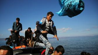MITILINI, GREECE - OCTOBER 13:  A boat carrying Syrian and Iraqi refugees arrives on the island of Lesbos from Turkey on October 13, 2015 in Mitilini, Greece. Dozens of rafts and boats are still making the journey daily as thousands flee conflict in Iraq, Syria and Afghanistan. More than 500,000 migrants have entered Europe so far this year. Of that number four-fifths of have paid to be smuggled by sea to Greece from Turkey, the main transit route into the EU. Nearly all of those entering Greece on a boat from Turkey are from the war zones of Syria, Iraq and Afghanistan.  (Photo by Spencer Platt/Getty Images)