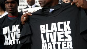SAN FRANCISCO, CA - DECEMBER 18:  A protestor holds a black lives matter t-shirt during a 'Hands Up, Don't Shoot' demonstration in front of the San Francisco Hall of Justice on December 18, 2014 in San Francisco, California. Dozens of San Francisco public attorneys and activists staged a 'Hands Up, Don't Shoot' demonstration to protest the racial disparities in the criminal justice system following the non-indictments of two white police officers who killed unarmed black men in Missouri and New York.  (Photo by Justin Sullivan/Getty Images)