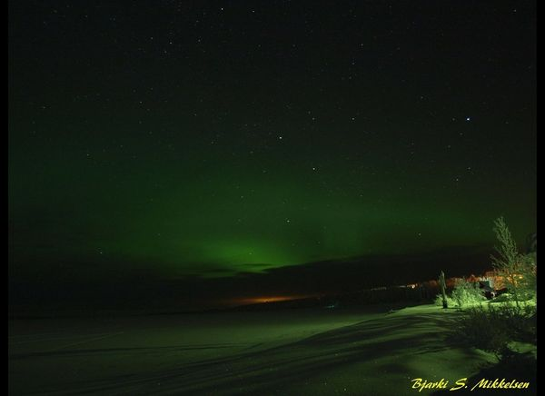 Iceland's Northern Lights and some city light in background <br><br><strong>Why Go</strong>: Leave the bustling nightlife of