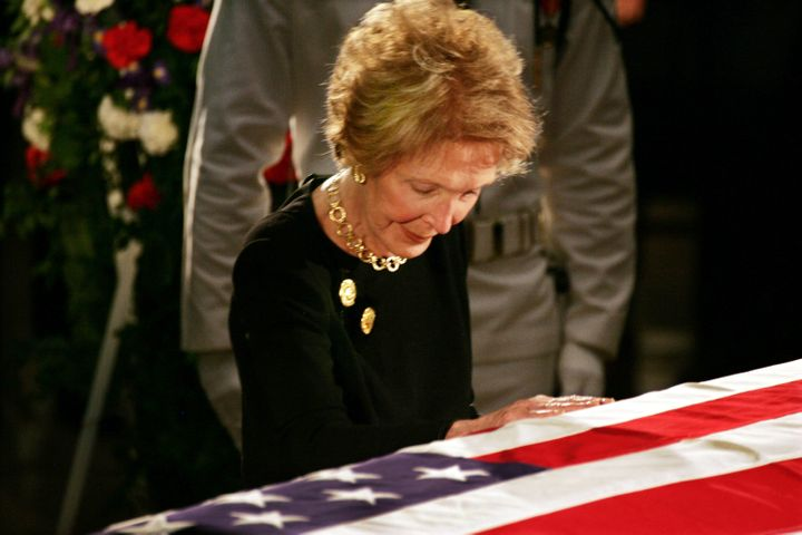 Nancy Reagan touches her husband'scasket as he lies in state inside the rotunda of the U.S. Capitol on June 9, 2004.