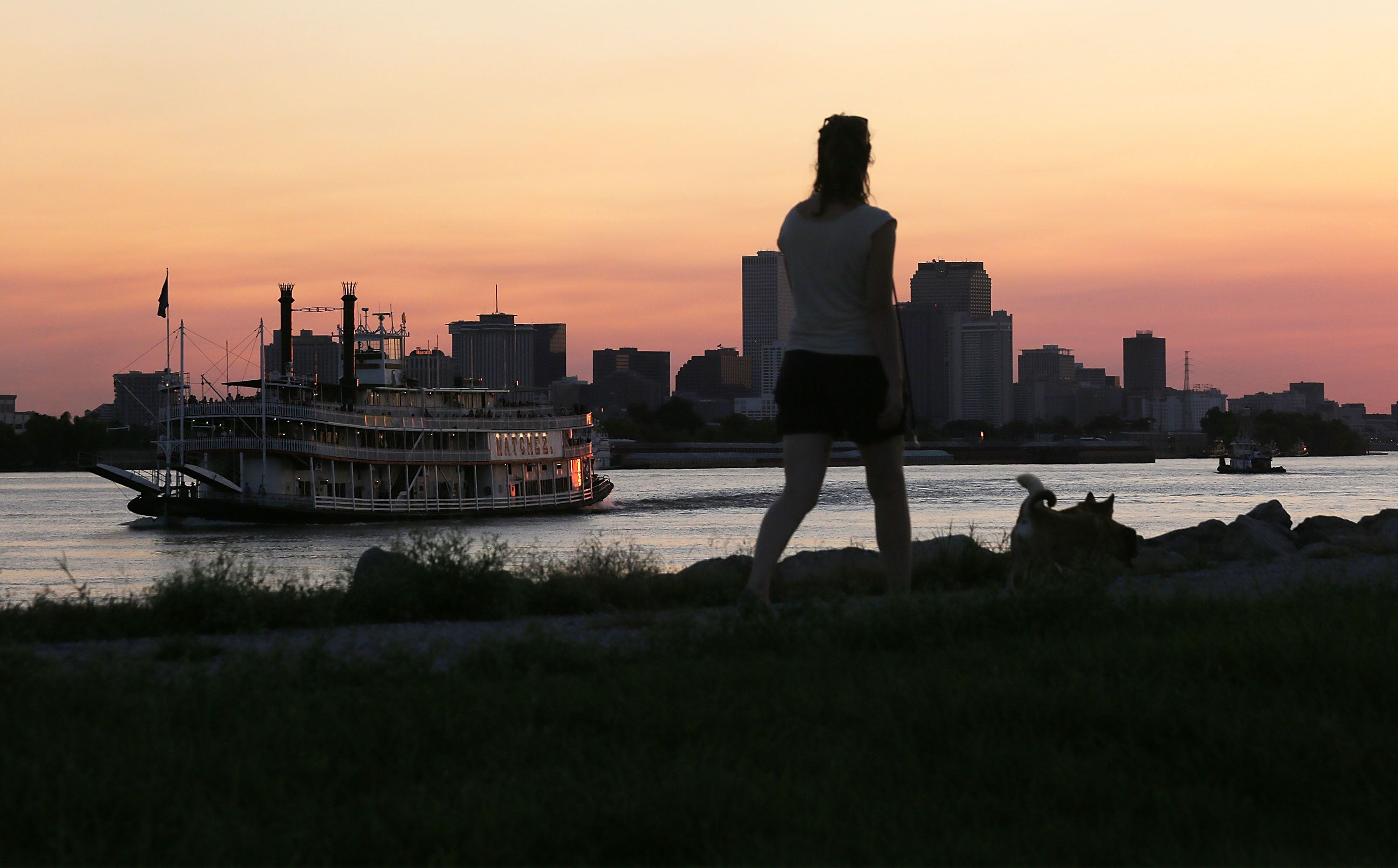 NEW ORLEANS, LA - AUGUST 26:  A woman walks atop an earthen levee on the Mississippi River in the Lower Ninth Ward as the Steamboat Natchez passes on August 26, 2015 in New Orleans, Louisiana.  New Orleans is ringed by hundred of miles of levees to protect against flooding. The tenth anniversary of Hurricane Katrina, which devastated the city partially due to levee breaches, is August 29.  (Photo by Mario Tama/Getty Images)